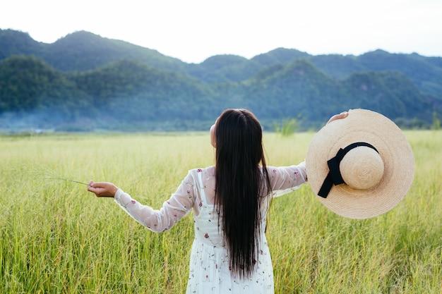 Der rücken einer schönen frau, die sich auf der wiese mit einem großen berg wie einer freut.