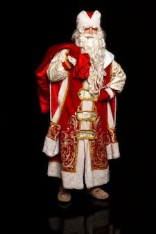 Der russische weihnachtsmann eilt mit geschenken zu den kindern. feststimmung. schwarzer hintergrund. vertikale.