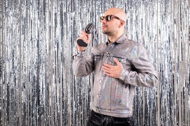 Der sänger der 90er jahre, der ein silbernes hemd und eine lederhose trägt, singt lieder