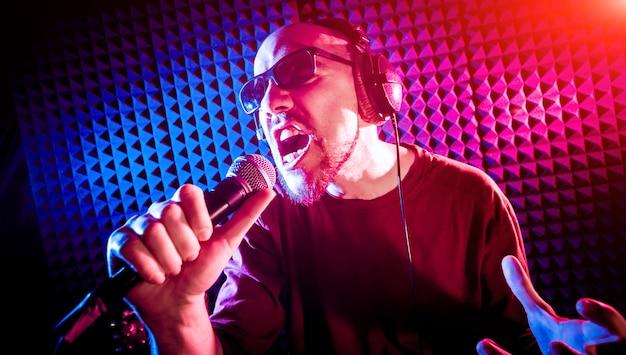 Der sänger singt mit einem mikrofon im tonstudio.