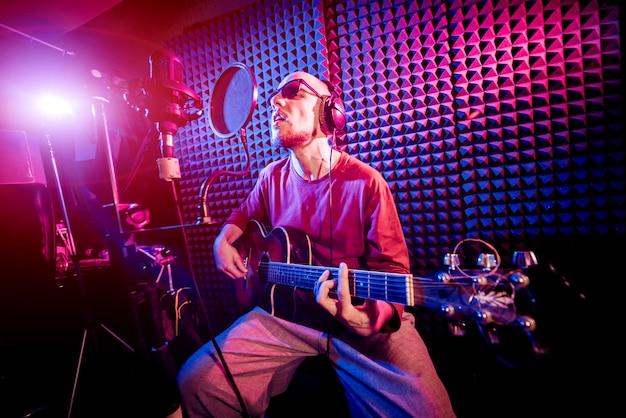 Der sänger singt mit einem mikrofon und spielt gitarre im tonstudio.