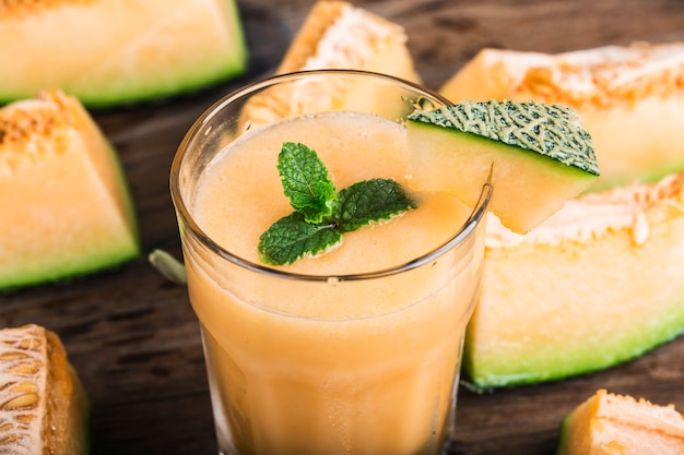 Der saft der melone mit minze in einem glasgefäß auf dem tisch. hamimelone