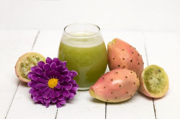 Der saft, der vom opuntia ficus-indica-kaktus gemacht wird, trägt auf einem weißen hintergrund früchte