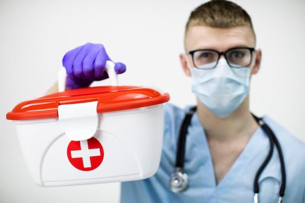 Der sanitäter in maske, brille und blauen latexhandschuhen hält einen medizinischen koffer mit rotem kreuz