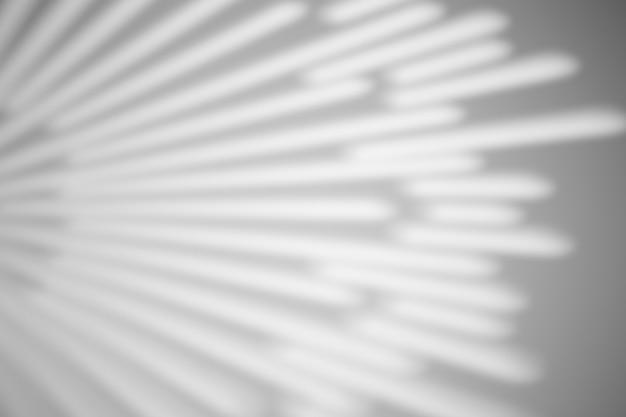 Der schatten von den strahlen auf einer weißen wand bei sonnigem wetter mit hellem licht. schattenüberlagerungseffekt für foto.