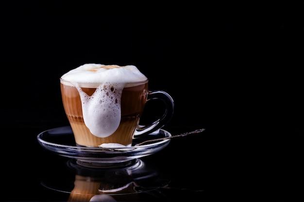 Der schaum in der kaffeetasse fließt über den rand.