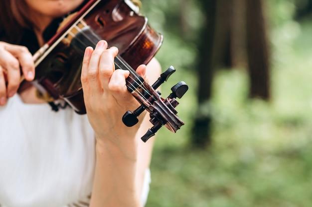 Der schauspieler tritt auf einer party auf. musikinstrument, hände einer geiger-nahaufnahme.