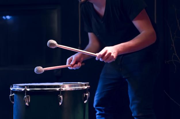 Der schlagzeuger spielt mit stöcken auf dem boden in einem dunklen raum mit wunderschöner beleuchtung. konzert- und performancekonzept.