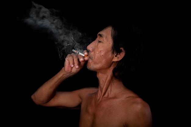 Der schlanke alte mann im porträt rauchte auf dem schwarzen hintergrund