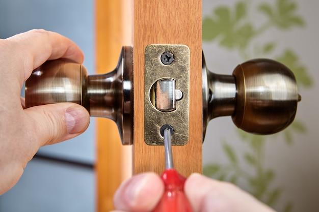Der schlosser installiert den türgriff mit schloss und befestigt den bolzen an der verriegelungsplatte.