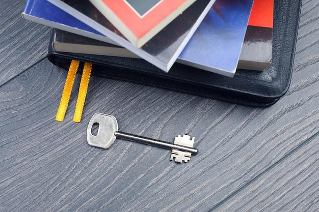 Der schlüssel liegt auf dem tisch vor dem hintergrund von büchern. metapher für die entdeckung von weisheit durch das studium der literatur