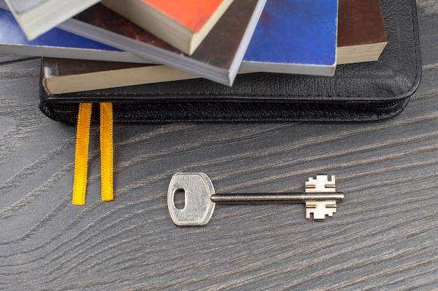 Der schlüssel liegt mit büchern auf dem tisch. metapher für die entdeckung von weisheit durch das studium der literatur