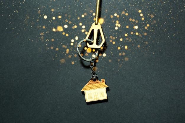 Der schlüssel zum haus mit goldenen pailletten und glühen auf schwarzem hintergrund. bauen, entwerfen, projektieren, in ein neues zuhause umziehen, hypotheken, buchungen, mieten und kauf von immobilien. neujahr, weihnachten