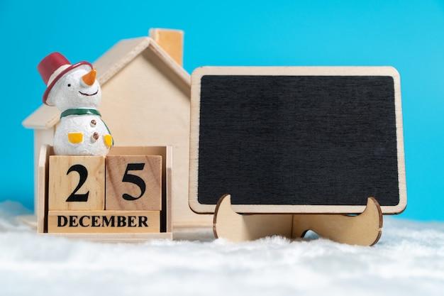 Der schneemann, der auf dem holzblockkalender sitzt, stellte am 25. dezember ein