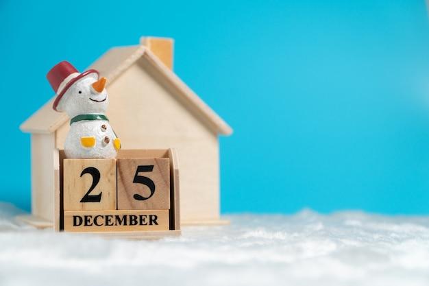 Der schneemann, der auf holzblockkalender sitzt, stellte am 25. dezember auf weiße wolle vor holz ein