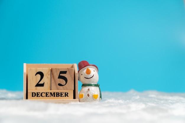 Der schneemann, der den roten hut sitzt neben holzblockkalender trägt, stellte am weihnachtsdatum 25 ein