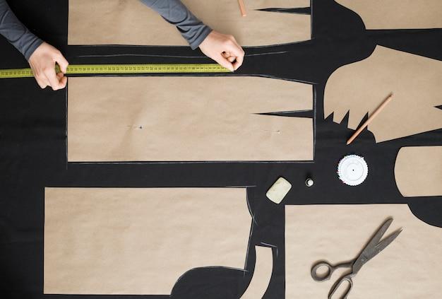 Der schneider legt das muster auf dem stoff im studio aus.