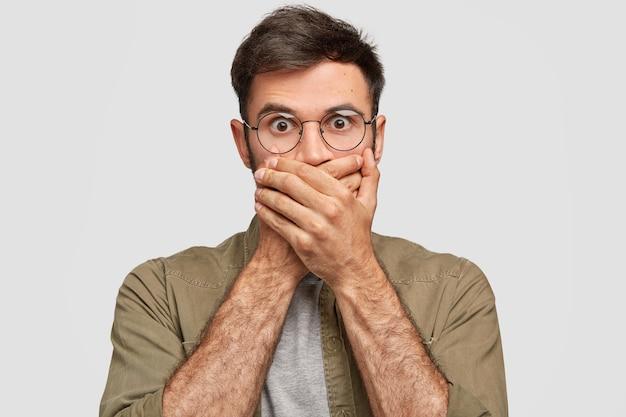 Der schockierte bärtige junge mann bedeckt den mund mit den händen, hat einen verängstigten ausdruck, starrt mit herausgesprungenen augen, ist sprachlos und stumm, isoliert über der weißen wand. menschen, reaktionskonzept