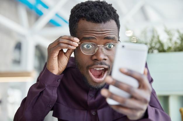 Der schockierte, dunkelhäutige junge mann starrt mit verwanzten augen, lässt den kiefer fallen und trägt eine transparente brille