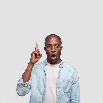 Der schockierte dunkelhäutige mann sieht mit verblüfftem gesichtsausdruck aus, zeigt mit dem zeigefinger nach oben, trägt ein jeanshemd, steht an der weißen wand und bemerkt etwas seltsames. ethnizität und emotionen