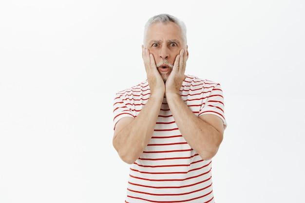Der schockierte und verblüffte alte bärtige mann reagiert auf atemberaubende neuigkeiten und sieht verwundert aus