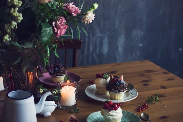 Der schöne festliche tisch mit rustikalem bouquet, cupcakes und kerzen. platz kopieren