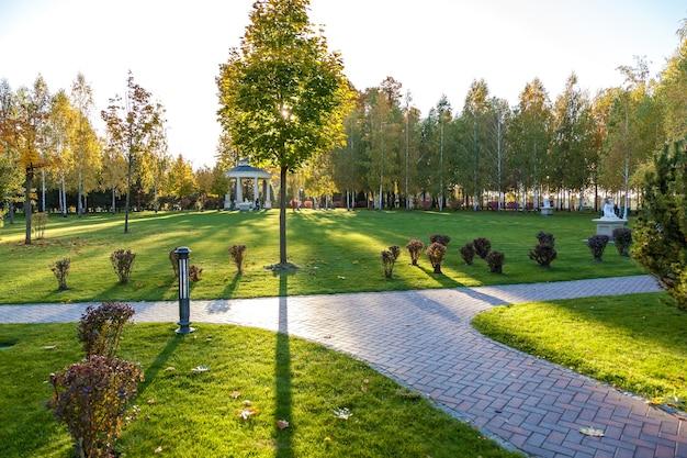 Der schöne park mit verschiedenen pflanzen und gereinigten rasenflächen. der steinweg erstreckt sich über die rasenflächen. im hintergrund befindet sich ein kleiner pavillon.