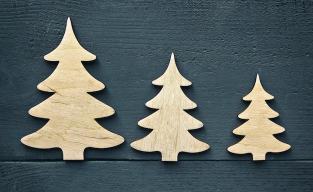 Der schöne weihnachtshintergrund mit drei kleinen holzdekorationen auf dem dunklen holzschreibtisch