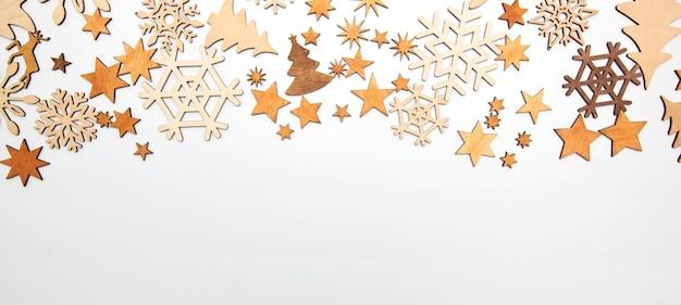 Der schöne weihnachtshintergrund mit vielen kleinen holzdekorationen auf dem weißen schreibtisch