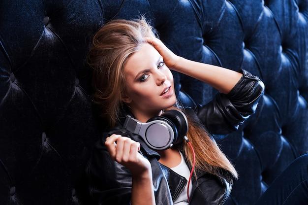Der schönste musikliebhaber. schöne junge frau mit kopfhörern, die hand in den haaren hält und in die kamera schaut, während sie sich an die schwarze wand lehnt