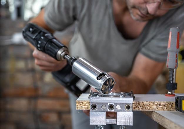 Der schreiner arbeitet mit einem professionellen präzisionsbohrwerkzeug.