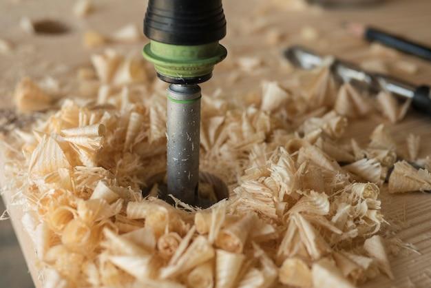 Der schreiner bohrt mit einem bohrer ein werkstück aus holz. ein bohrer, ein stift und eine ecke
