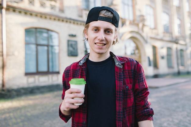 Der schüler hält eine tasse kaffee in der hand und zeigt mit dem daumen nach oben