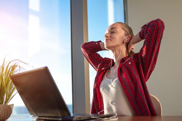 Der schüler macht eine pause, während er online lernt und musik über kopfhörer hört