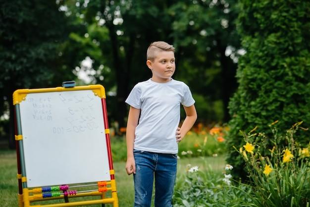 Der schüler schreibt unterricht an die tafel und ist im outdoor-training tätig. zurück zur schule, lernen während der pandemie.