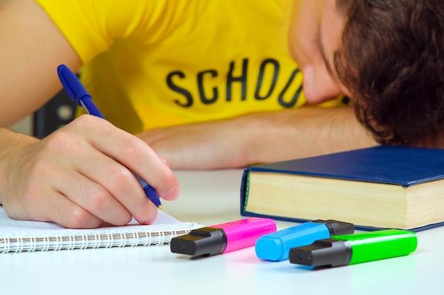 Der schüler sitzt mit einem lehrbuch und einem notizbuch an einem tisch und ist gelangweilt. thema ist von geringem interesse, zu faul, um aufgaben zu erledigen.