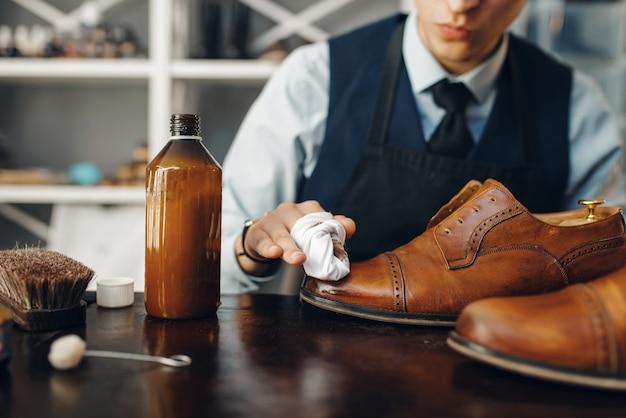 Der schuhmacher poliert den schuh- und schuhreparaturservice. handwerkskunst, schuhmacherwerkstatt, meisterarbeiten mit stiefeln, schuster