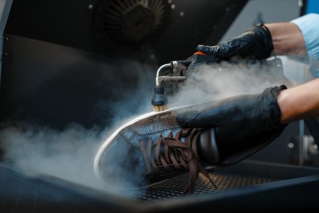 Der schuhmacher verarbeitet die schuhe auf einer speziellen maschine, einem reparaturservice für schuhe. handwerkskunst, schuhmacherwerkstatt, meisterarbeiten mit stiefeln, schusterladen