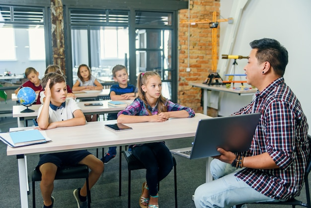 Der schuljunge sitzt zusammen mit seinen klassenkameraden hinter dem schreibtisch und hebt die hand, um dem lehrer während des unterrichts in der grundschule fragen zu stellen.