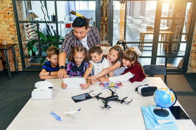 Der schullehrer am schreibtisch arbeitet mit fünf jungen schülern, die im technologieunterricht einen digitalen tablet-computer verwenden.