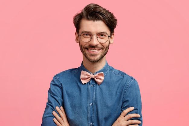 Der schuss eines glücklichen eleganten jungen mannes drückt die hände, sieht mit freudigem ausdruck aus, hat ein freundliches lächeln, trägt ein elegantes jeanshemd mit fliege, isoliert über der rosa wand. froher männlicher freiberufler