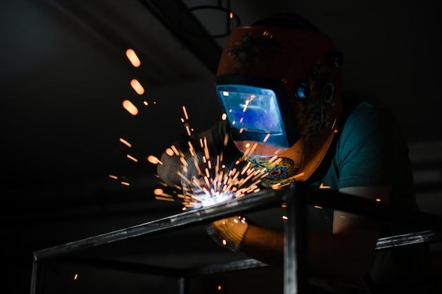 Der schweißer arbeitet mit einem schweißlichtbogen über einer metallstruktur