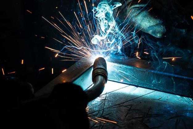 Der schweißer kocht den rahmen. der schweißer kocht das metall. der schweißer kocht metallstrukturen. schweißen funktioniert. funken, geschmolzenes metall