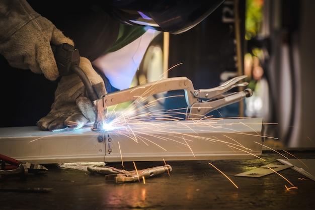 Der schweißer schweißt die metallteile im automobilmontagewerk und übt die fähigkeiten des schweißers in industrieanlagen.