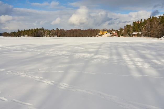Der see ist in littoinen, finnland, mit eis und schnee bedeckt.