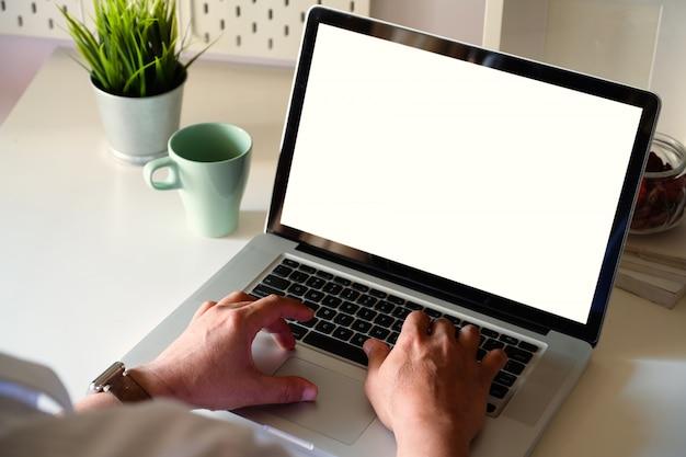 Der seitenansichtmann, der mit laptop arbeitet, ist auf der arbeitstabelle in einem conner-büro