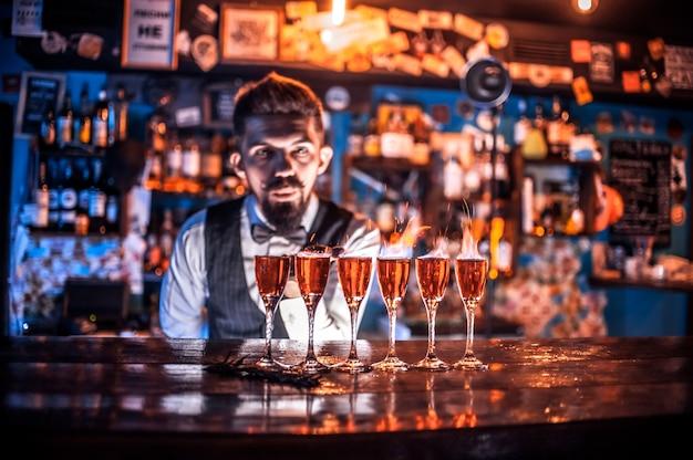 Der selbstbewusste barkeeper demonstriert seine beruflichen fähigkeiten, während er in der bar neben der theke steht