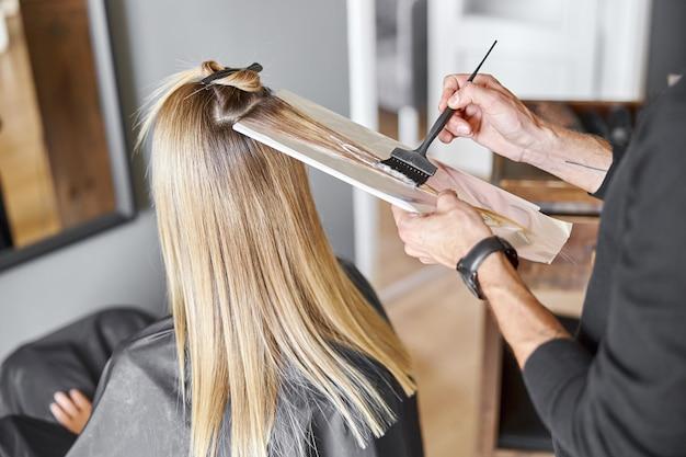 Der selbstbewusste männliche stylist färbt die haare einer blonden kaukasischen kundin