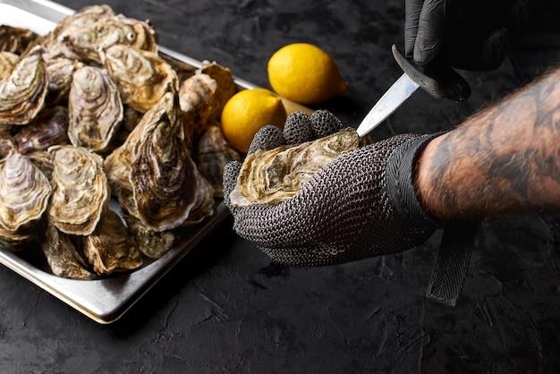 Der selektive fokus bereitet frische austern auf der arbeitsplatte des meeresfrüchte-standes auf dem markt zu