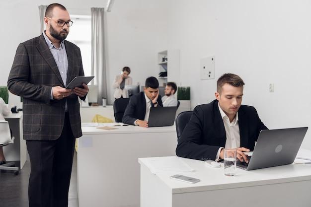 Der senior manager überprüft die qualität der aufgaben seiner junior-mitarbeiter, die an einem computer im büro eines finanzunternehmens sitzen.
